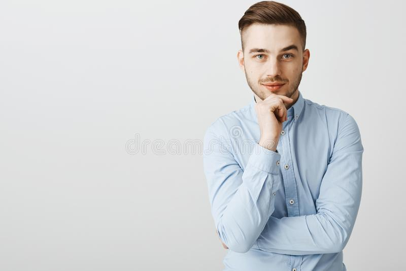 Smart ambitiös stilig man i moderiktig för skjortainnehav för blå krage hand på hakan som smilar från att stirra för intresse och royaltyfria foton