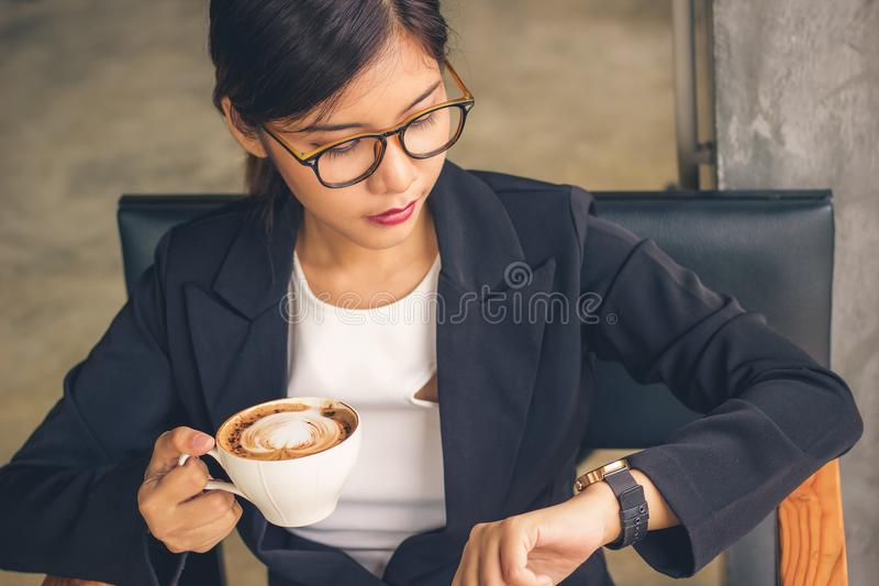 Smart Asian business woman holding mocha latte art coffee. Smart Asian business woman holding mocha latte art coffee and looking watch time royalty free stock photos