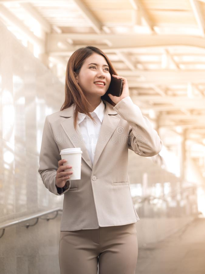 Free Smart Asian Business Woman In A Suit With Mobile Phone And Holding A Paper Cup Of Coffee, Outside Corporate Office. Stock Photo - 114197160