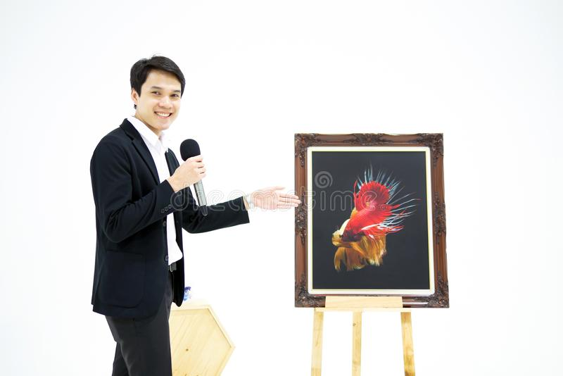 Smart Asian men is presenting the beautiful siamese fighting fish (betta) photo in the museum exhibition. stock photos