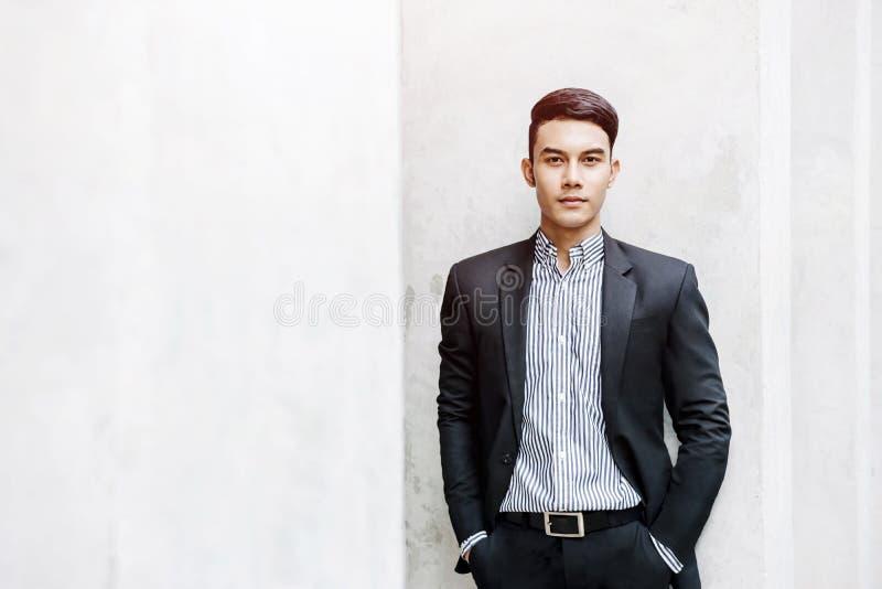 Smart asiatisk affärsman i den tillfälliga dräkten som ser kameran med F royaltyfri fotografi