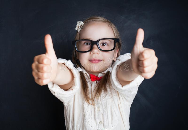 Smart barnliten flicka med tummen som har upp gyckel i klassrum arkivbilder
