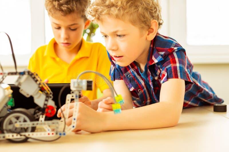 Smart blond pojke som försöker att konstruera en robot royaltyfri foto