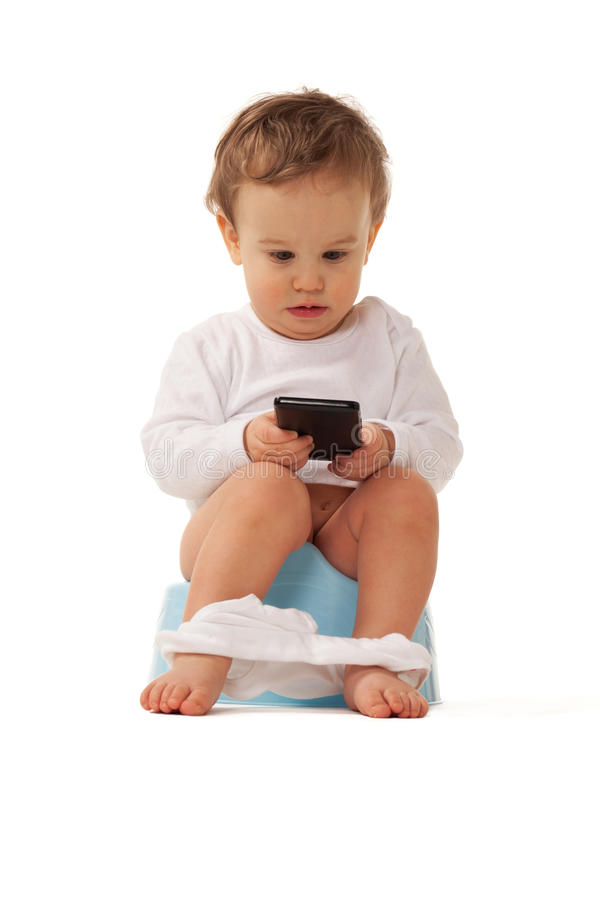 Smart boy. Boy sitting on a chamber bot playing with smartphone royalty free stock images