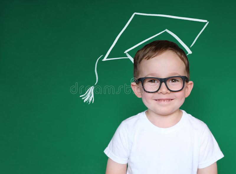 Smart Boy with Glasses, School Kid in Chalk Hat over Blackboard, Education Concept stock photo