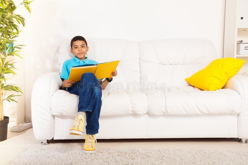 Smart boy reading literature stock image