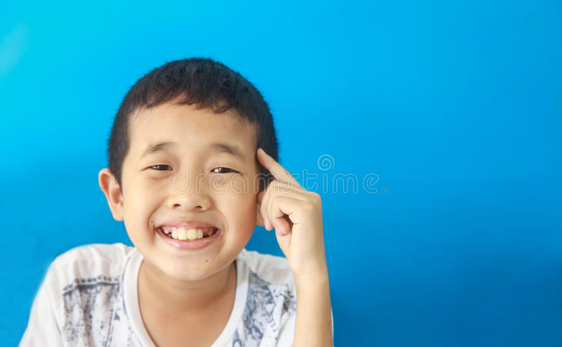 Smart boy think and get idea then smile. Against blue background stock photo