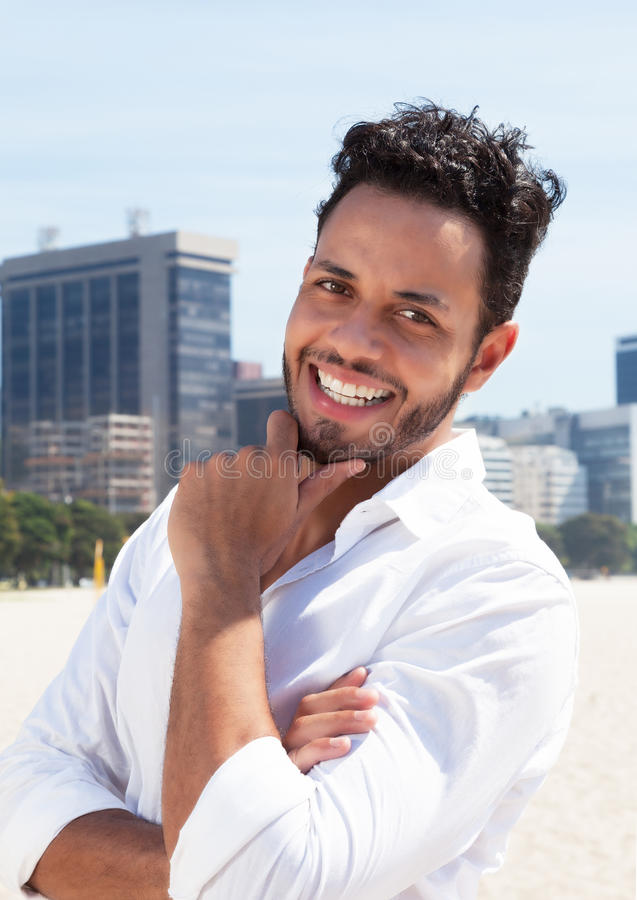 Smart brazilian man with skyline in the background. Smart brazilian man laughing at camera with blue sky and skyline of a modern city in the background stock photo