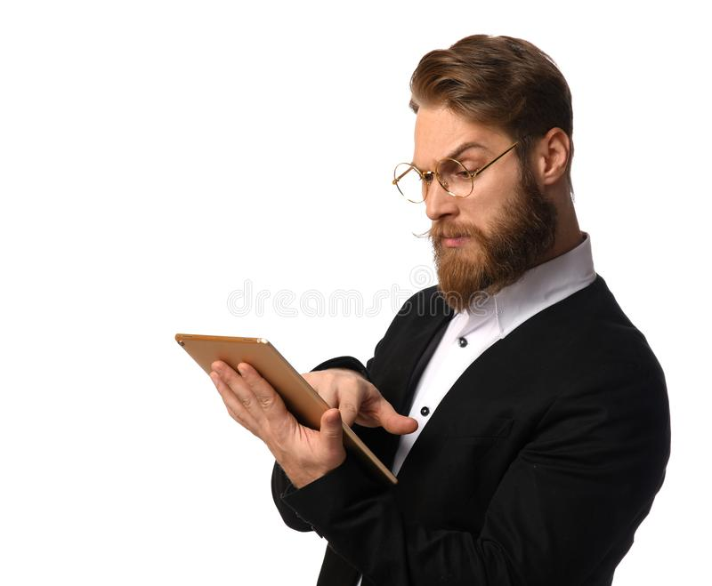 Smart business man in black suit and white shirt make a purchase online using tablet computer in glasses royalty free stock photo