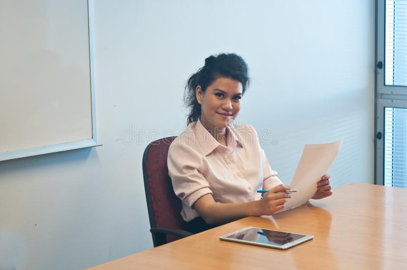 Smart business woman examining contract agreement in office. Smart and confidence Asian business woman examining contract agreement in office stock image