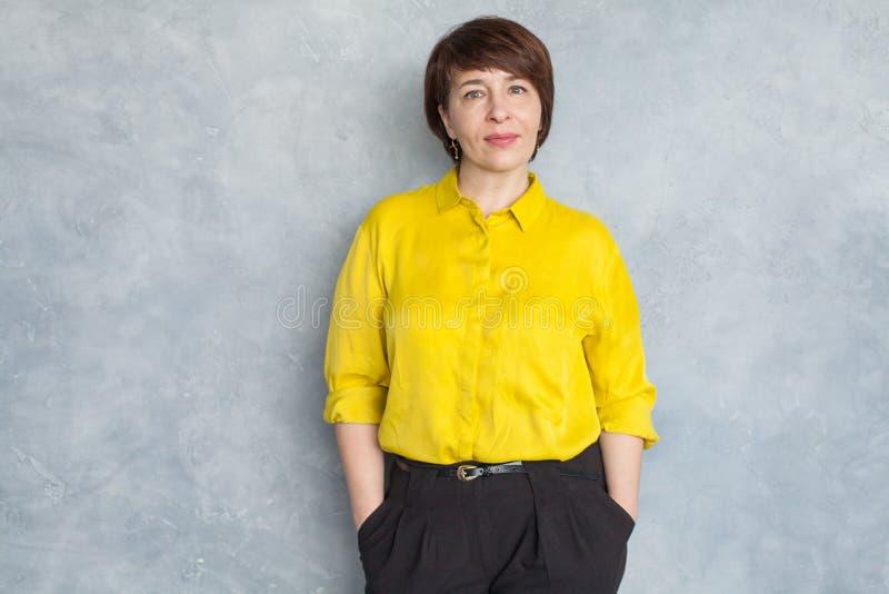 Smart business woman wearing yellow shirt. Mature woman 45 years old stock image