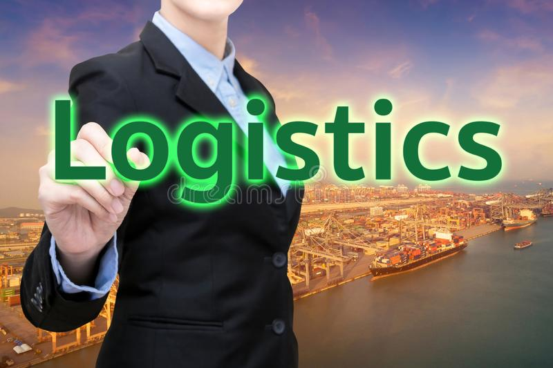 Smart business woman writing Logistics word with shipping boat at logistics yard. In background stock images