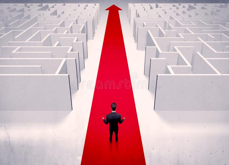Smart businessman avoiding maze concept. An adult elegant businessman standing on a red carpet arrow pointing ahead through a street with maze on two sides stock photo