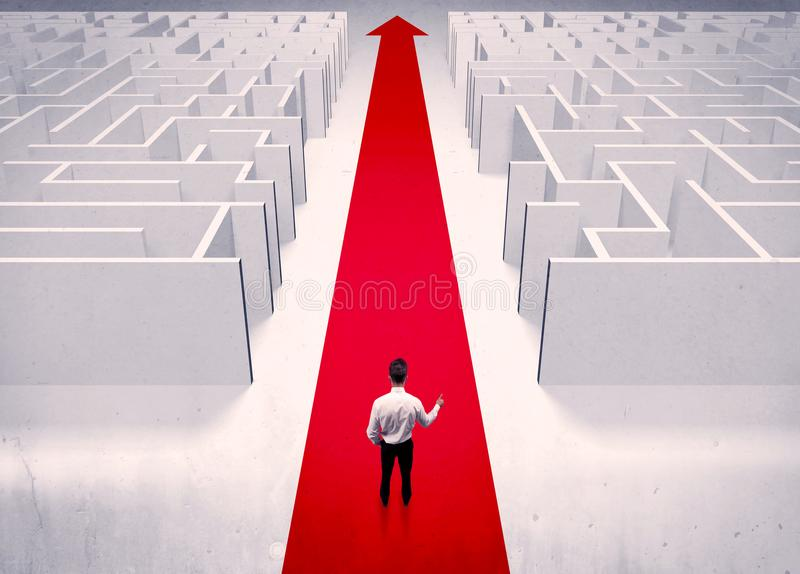 Smart businessman avoiding maze concept. An adult elegant businessman standing on a red carpet arrow pointing ahead through a street with maze on two sides stock images