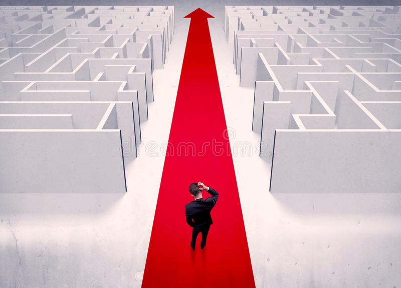 Smart businessman avoiding maze concept. An adult elegant businessman standing on a red carpet arrow pointing ahead through a street with maze on two sides royalty free stock images
