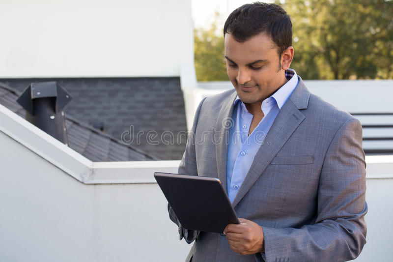Smart businessman. Closeup portrait, man in gray suit blazer doing business on tablet, outside outdoors background royalty free stock images