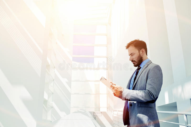 Smart businessman dressed in luxury suit holding touch pad while standing in modern office space with big copy space area for your stock photography