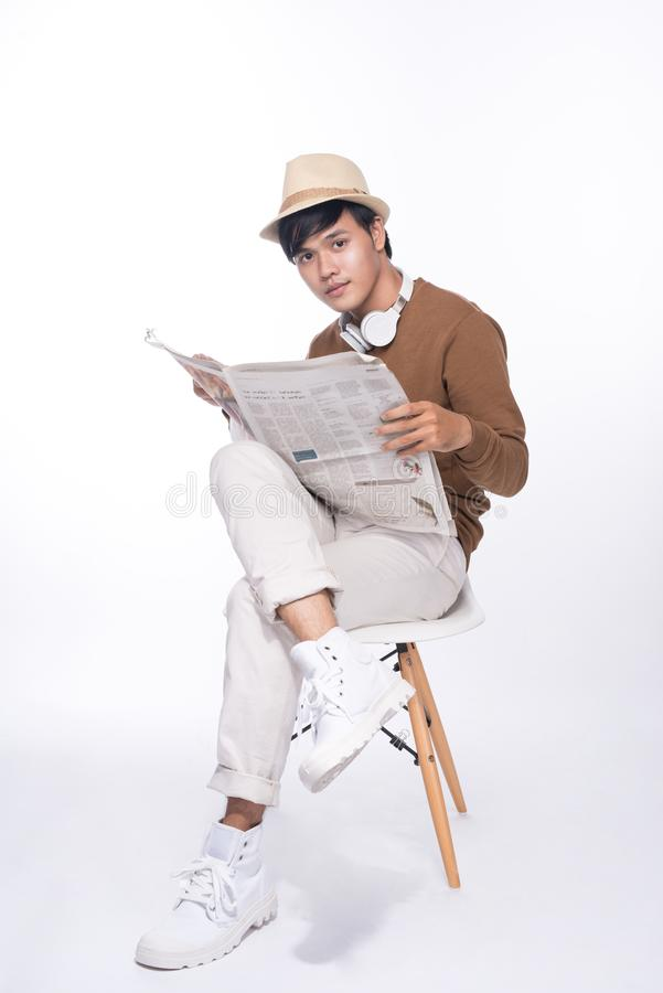 Smart casual asian man seated on chair, reading newspaper in stu royalty free stock image
