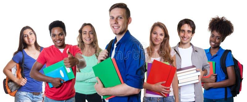 Smart caucasian manlig student med gruppen av internationella studenter royaltyfri foto