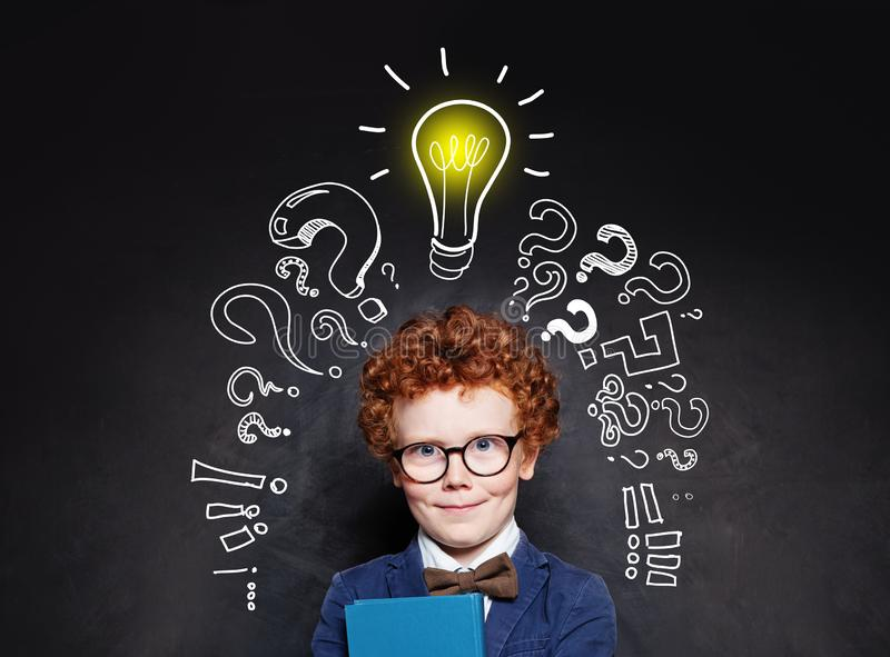 Smart child boy in glasses smiling and holding book on background with lightbulb royalty free stock images