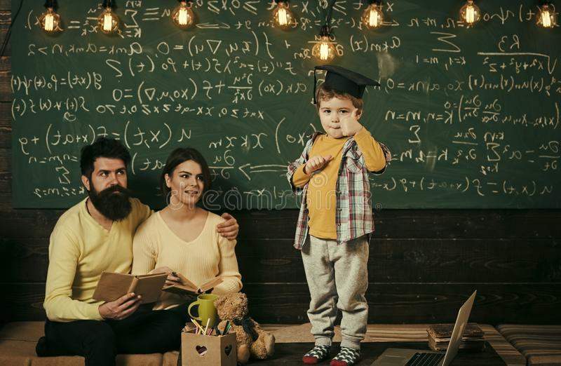 Smart child in graduate cap shows thumb up gesture. Boy presenting his knowledge to mom and dad. Parents listening their. Son, checking mistakes with book royalty free stock images