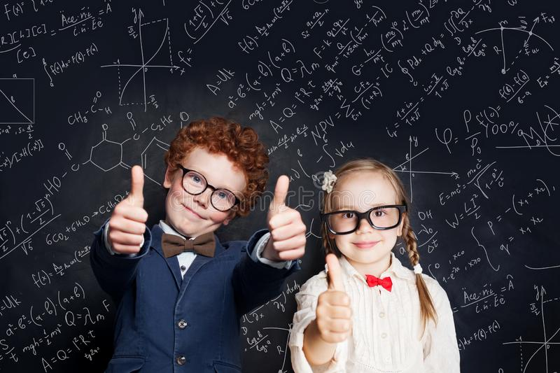 Smart children student having fun on blackboard background with science and maths formulas royalty free stock photo