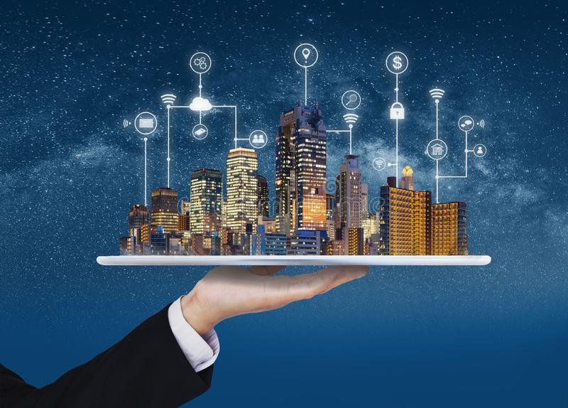 Smart city, building technology, and real estate business. Businessman holding digital tablet with buildings hologram. And application programming interface royalty free stock photos