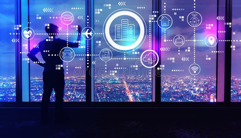 Smart city concept with man by large windows at night stock image