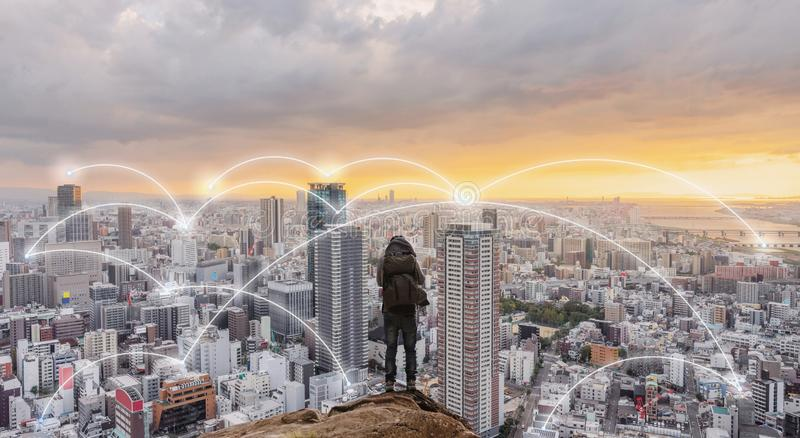 Smart city, wireless network and internet system in the city. Businessman standing on mountain peak with cityscape in sunset royalty free illustration