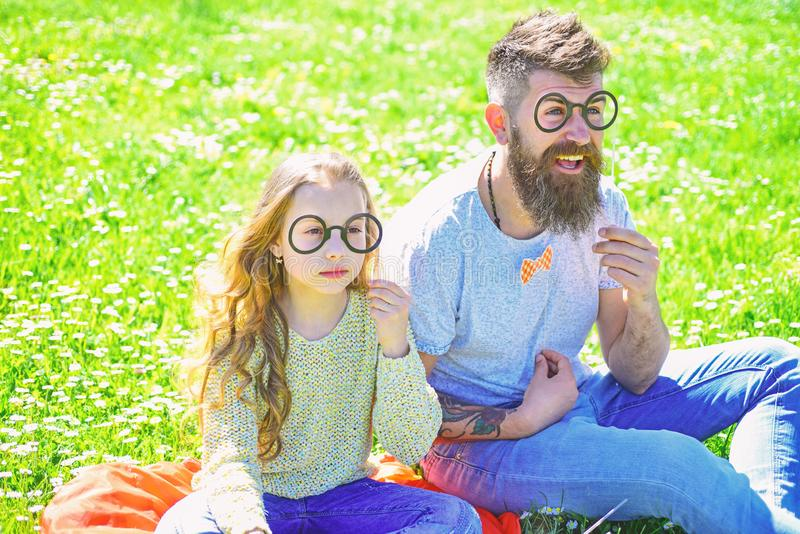 Smart and clever concept. Dad and daughter sits on grass at grassplot, green background. Child and father posing with. Eyeglases photo booth attributes at stock photography