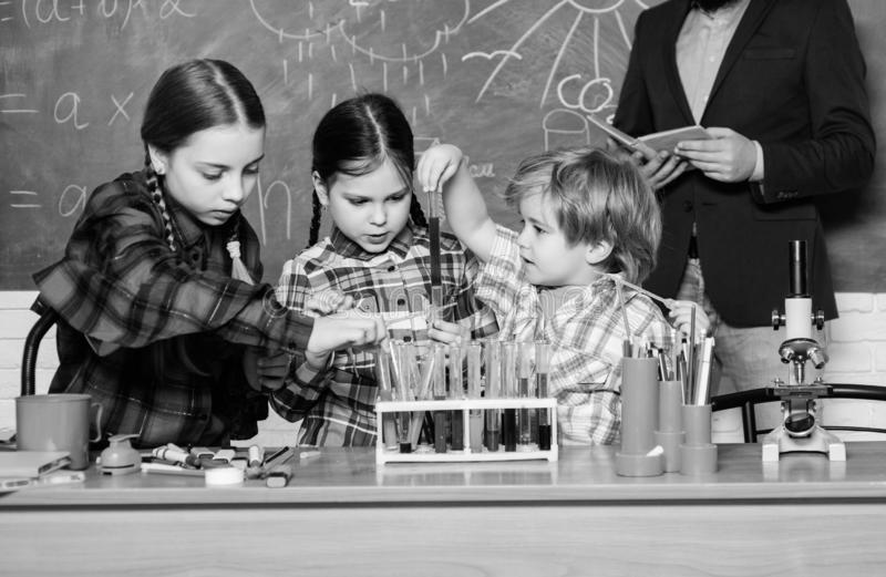Smart and confident. happy children teacher. back to school. experimenting with chemicals or microscope at laboratory. Biology education. Microscope. Biology stock images
