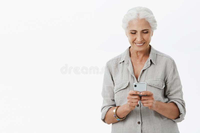 Smart and creative granny uses smartphone easily. Portrait of charming pleased senior woman with grey hair holding royalty free stock photo