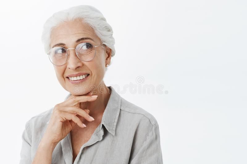 Smart creative and pleased charming granny with white hair in sight glasses smiling curiously holding hand above chin royalty free stock images