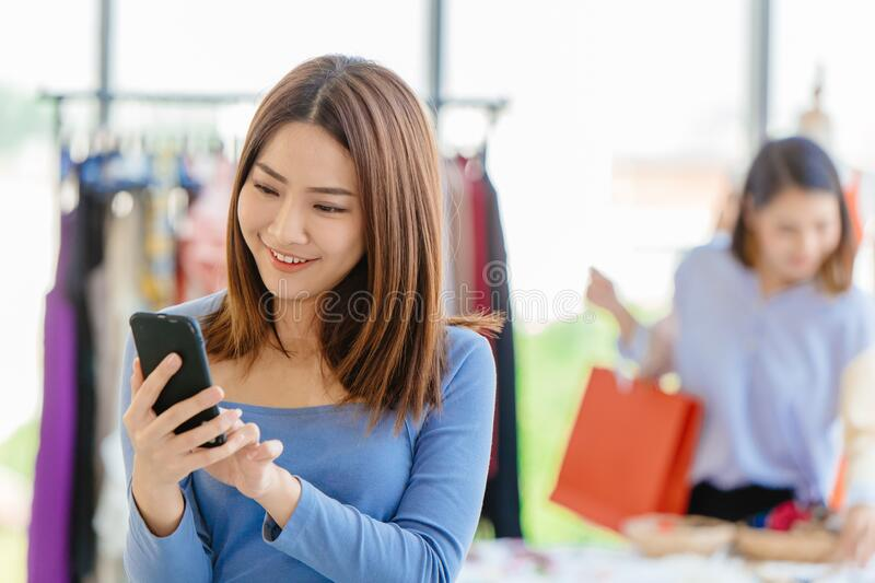 Smart customer using mobile phone to finding promotion search sale item and payment in shopping store.  stock image