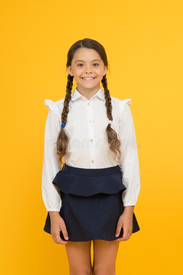 Smart cutie. Cute little girl smiling on yellow background. Happy small girl wearing school uniform. Primary school girl stock image