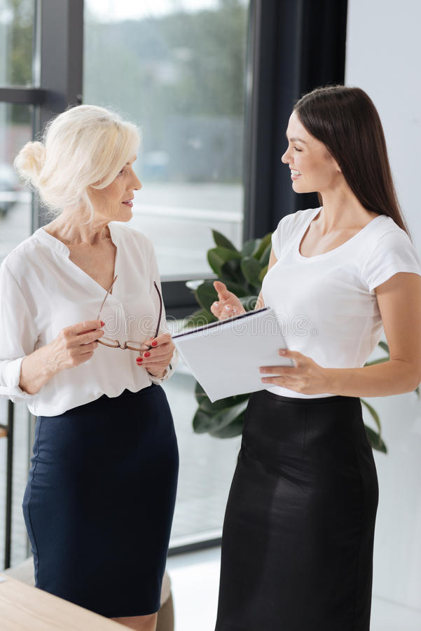 Smart delighted colleagues talking to each other. Work issues. Smart delighted female colleagues looking at each other and talking while discussing work royalty free stock photos