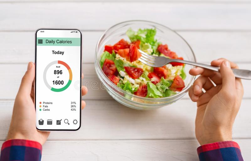 Man eating vegetable salad and counting calories on mobile application. Smart eating and diet planning concept. Man eating fresh vegetable salad and counting stock photo