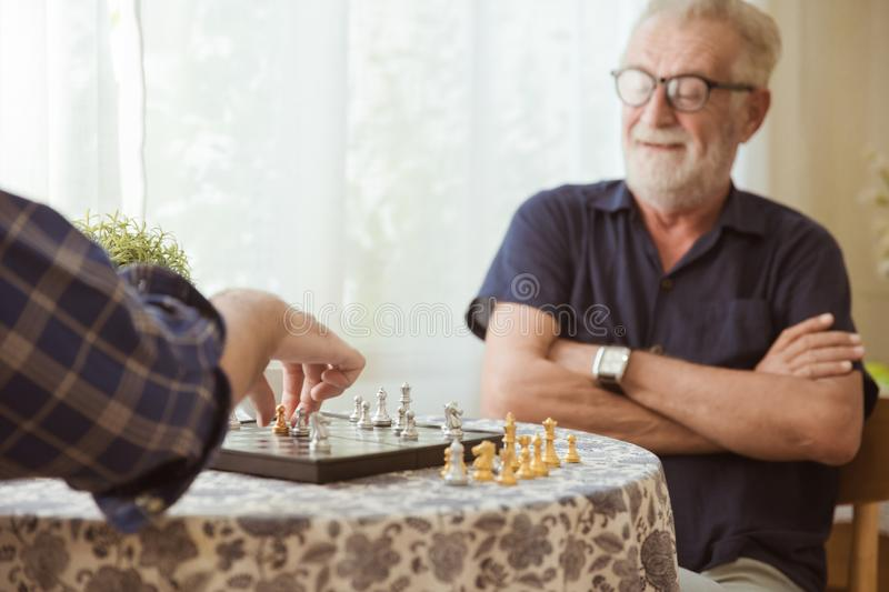 Smart Elder playing Chess board game at home for training brain memory and thinking happy smiling selective focus at chess piece royalty free stock image