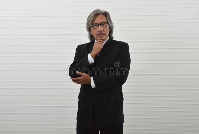 Smart elderly asian businessman in black suit and eyeglasses holding his hand on his chin over white wall background, Business stock images