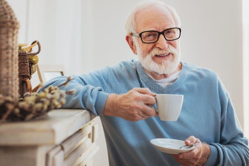 Smart elderly man drinking coffee while having break royalty free stock photos