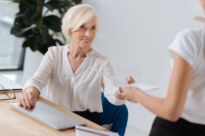 Smart elderly woman taking documents stock image