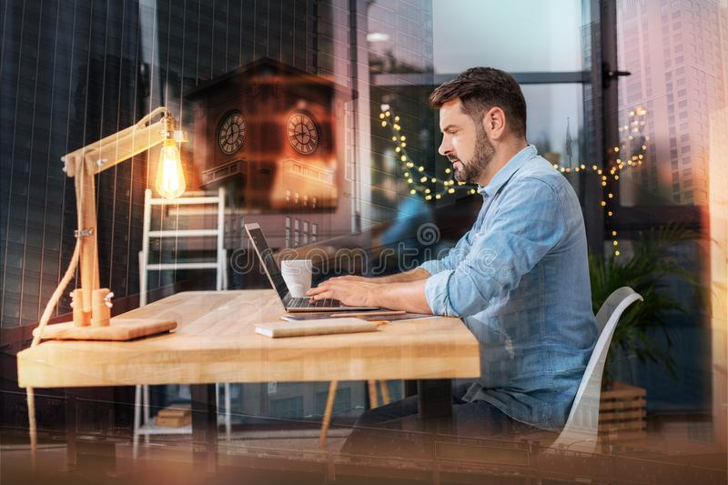 Smart employee sitting at the table and typing a letter. Concentrated worker. Calm clever experienced employee having a productive day at home while sitting at royalty free stock images