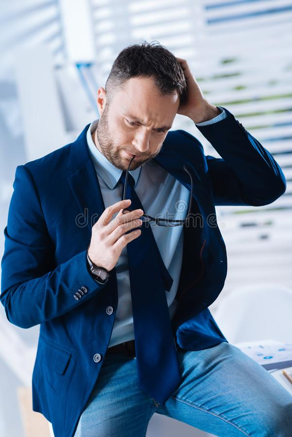 Smart enthusiastic businessman holding glasses while sitting and thinking stock photos