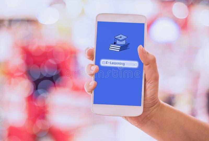 Smart för kvinnahandhåll som telefon direktanslutet e-lär på mobil, med bokehbakgrunder, begrepp och internetläs-och skrivkunnigh royaltyfri bild