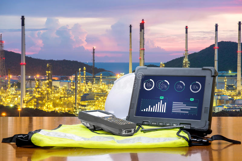 Smart factory - Rugged computers tablet in front of oil refinery. Industry royalty free stock photography