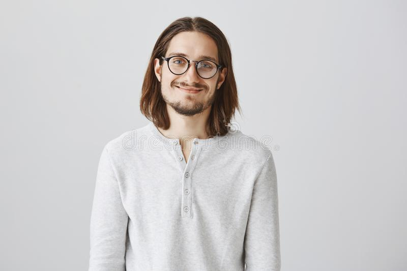 Smart and friendly scientist asking out cute coworker. Portrait of happy charming male with long hair, wearing glasses stock image