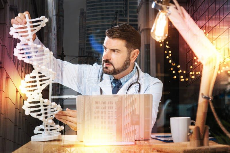 Smart genetiker som rymmer en stor DNAmodell, medan vara på arbete arkivbild