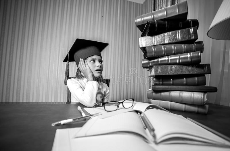 Smart girl in graduation cap looking at high heap of books. Black and white portrait of smart girl in graduation cap looking at high heap of books royalty free stock images
