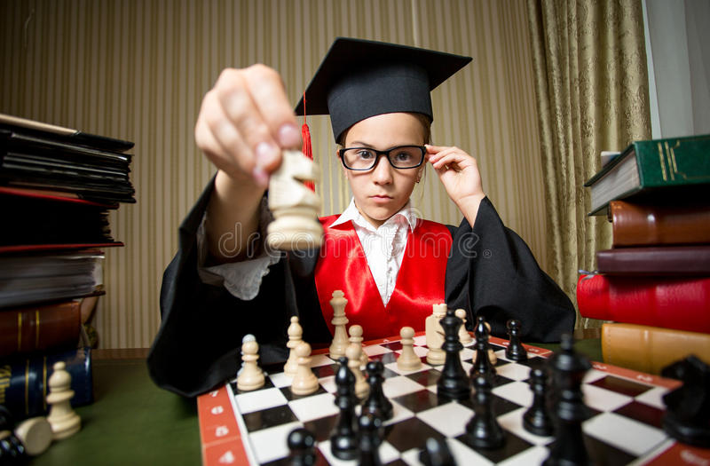 Smart girl in graduation cap making move at chess with horse. Closeup portrait of smart girl in graduation cap making move at chess with horse royalty free stock image