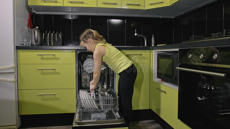 Smart girl learning to use dishwasher. Stylish modern Built In Kitchen Appliances in green black. Child is putting clean. Smart girl learning to use dishwasher royalty free stock image
